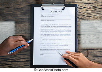 Two Person's Hand Reviewing Contract Form