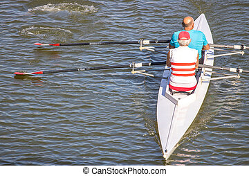 Two persons rowing boat on Arno River, Florence, Italy