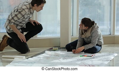 Two persons sit on floor and discuss plan of building