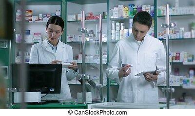 Two pharmacists working in pharmacy drugstore