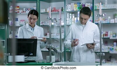 Two pharmacists working in pharmacy drugstore - Two...