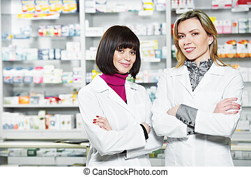Two Pharmacy chemist women in drugstore - Two cheerful...