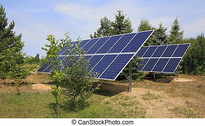 Two photovoltaic panels set in backyard against trees and...
