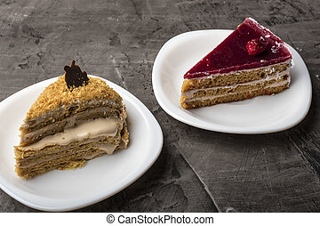 Two pieces of cake on a dark background. Honey and raspberry dessert
