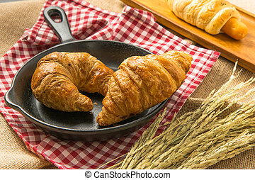 Two pieces of croissant on black ceramic pan that put on the...