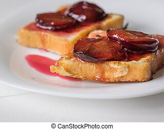 Two pieces of French toast drizzled with plum jam on a white...