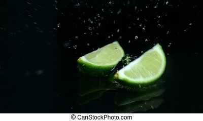 Two pieces of lime fall into the water. Black background. Slow motion