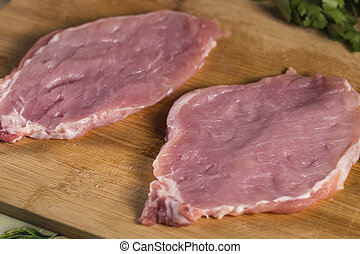 Two pieces of raw pork meat beaten to make schnitzels