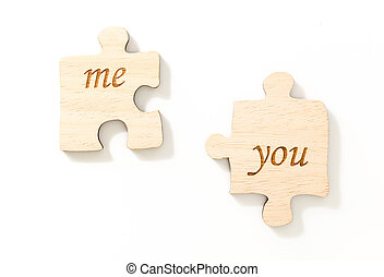 Two pieces of wooden puzzle, with text me & you, on white background.