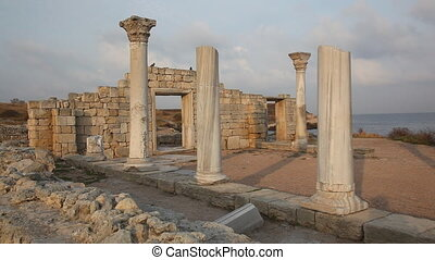 Two pigeons fly up and sit down on ruins of the ancient...