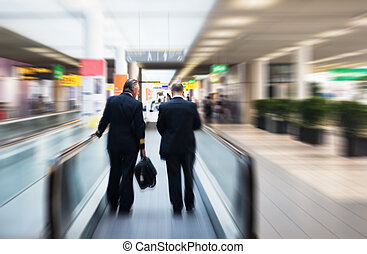 two pilots on a moving escalator