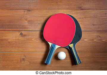 Two ping-pong rackets and a ball on a brown wooden background