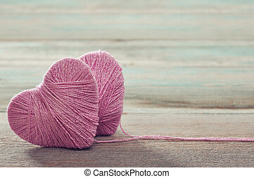 Two pink clews in shape of heart on vintage wooden...