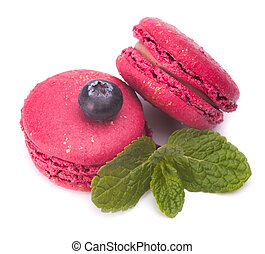 two pink macaroons with sprig of mint isolated