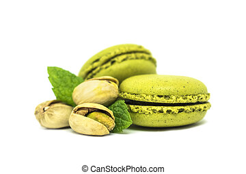 two pistachio macarons with nuts isolated on white