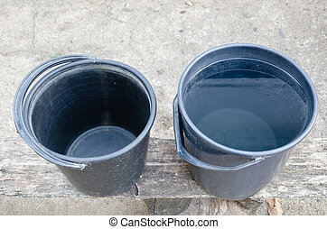 Two plastic buckets, one full, one empty