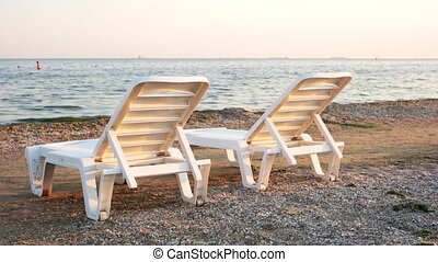 Two plastic chaise longues on seashore.