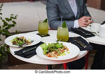 Two plates of fresh salad with arugula, mozzarella,...