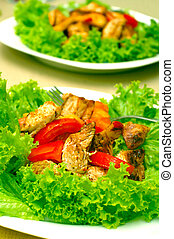 Hot Chicken salad with lettuce, apples and tomatoes.