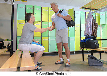 two players hand-shaking in locker room in the gym