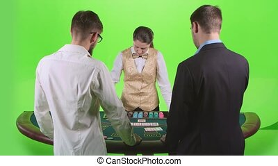 Two players play the poker in casino at the green table. Green screen. Slow motion