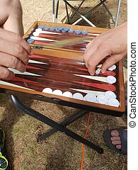 Two players playing backgammon board game