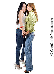 Two playful beauty young women in jeans. Isolated