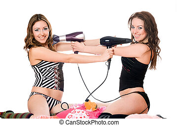 Two playful girlfriends with hair dryers. Isolated