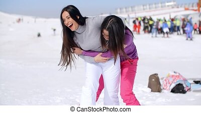 Two playful woman frolicking in the snow - Two playful...