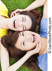 two pleasure young woman lying on grass
