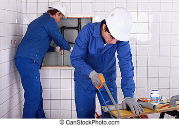 Two plumbers hard at work