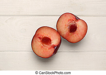 Two plums on the table. Close up. White background