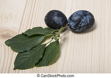 Two plums with green leaves