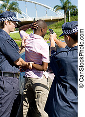 arrest - two police officers arresting a rowdy criminal