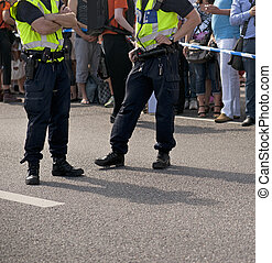 Two policemen keeping an eye on the crowd during a...