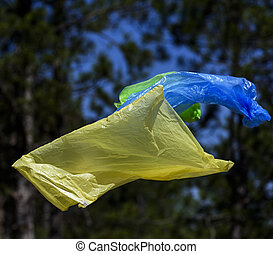 Two polyethylene bags for garbage fly in the air against the background of a pine forest
