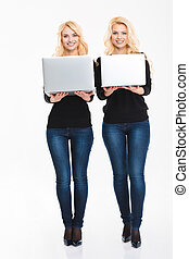 Two positive young blonde sisters twins with laptop computers