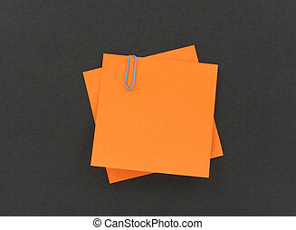 two post-it notes with a paperclip on black background