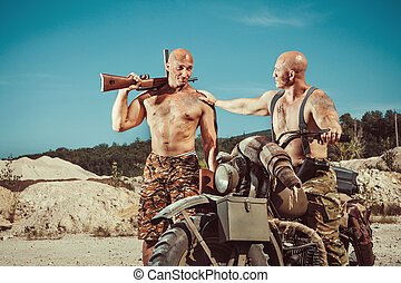Two power bikers with guns on the desert background.