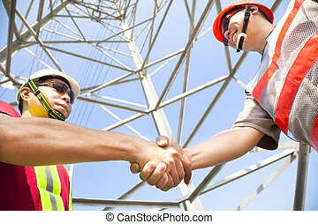 two power line tower workers with handshaking