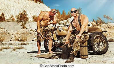 Two powerful soldiers are repairing old motorbike on the desert background.