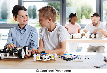 Two pre-teen students socializing during robotics class