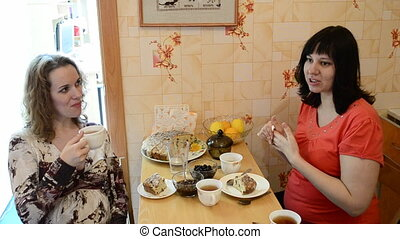 Two pregnant women drink tea