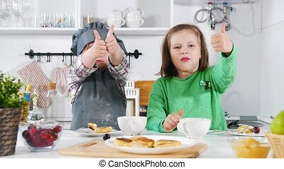 Two preschool girls bakers eats cooked cheesecakes and shows...