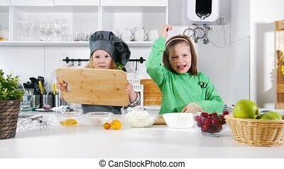 Two preschool little girls bakers have fun during cooking...