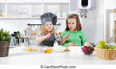 Two preschool little girls bakers playing and have fun...