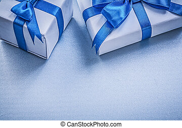 Two present boxes on blue background holidays concept