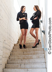 Two pretty businesswoman talks on the stairs