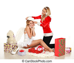 Two pretty christmas girl try on a Santa hat, on white