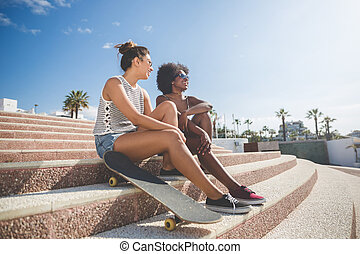 Two pretty female friends relaxing on stairs outside